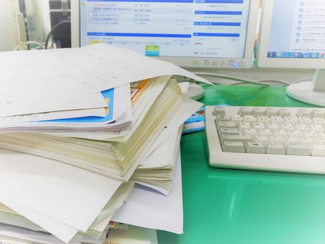 パソコンと書類の山